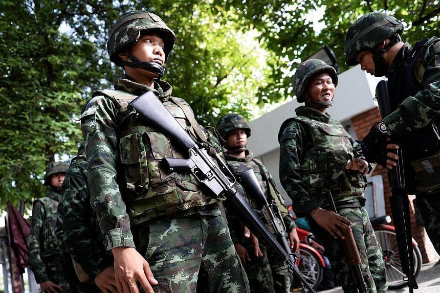 Thai soldiers stand outside the Government Public Relations Department after martial law was imposed in Bangkok on May 20, 2014. -- PHOTO: AFP