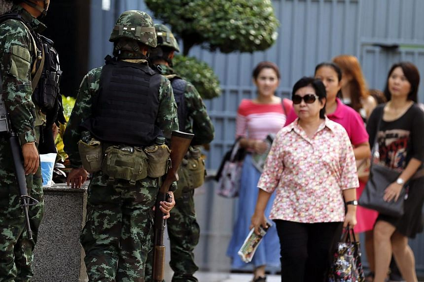 Thai office workers walk past armed soldiers standing guard outside the Shinawatra Tower Two in Bangkok, Thailand on May 20, 2014. -- PHOTO: EPA