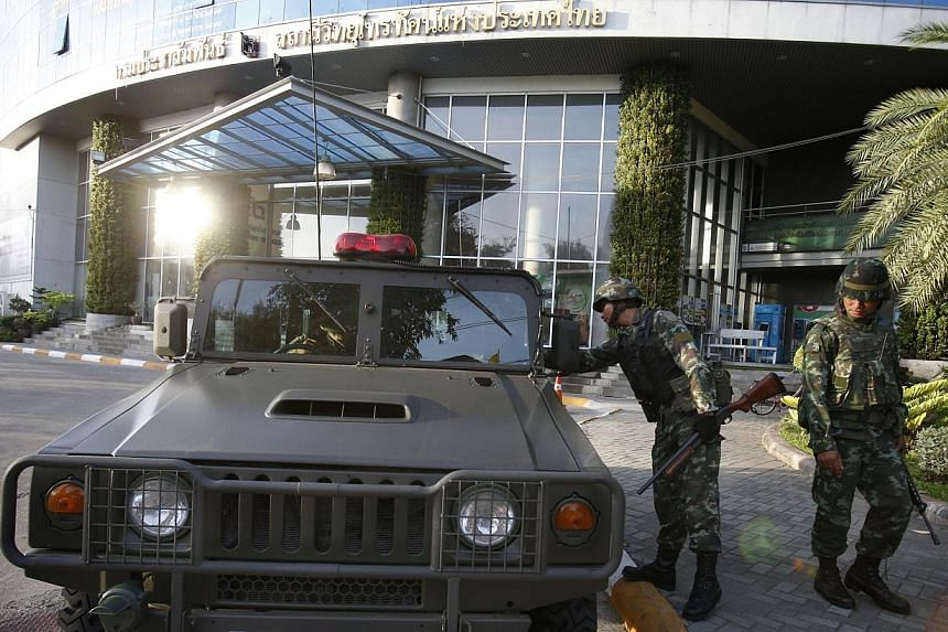 Thai soldiers stand in front of the National Broadcasting Services of Thailand television station in Bangkok on May 20, 2014. -- PHOTO: REUTERS