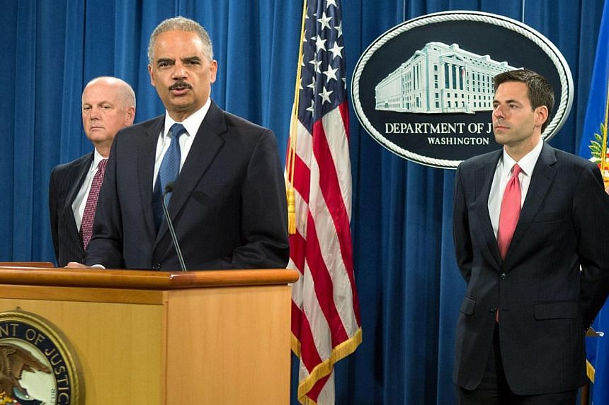 United States Attorney General Eric Holder (2nd left) announces the indictments of five Chinese nationals on cyber espionage charges for allegedly stealing trade secrets from American companies, during a news conference at the Justice Department in W