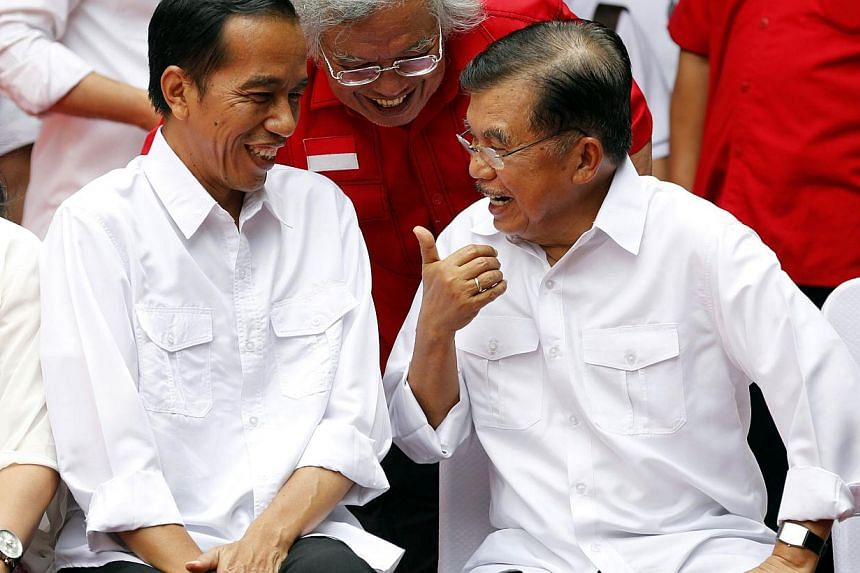 """Indonesian presidential candidate Joko """"Jokowi"""" Widodo (L) chats with his vice presidential running mate Jusuf Kalla (R) during an event declaring their bid in the upcoming July 9 election, in Jakarta May 19, 2014. Jokowi received a major boost in th"""
