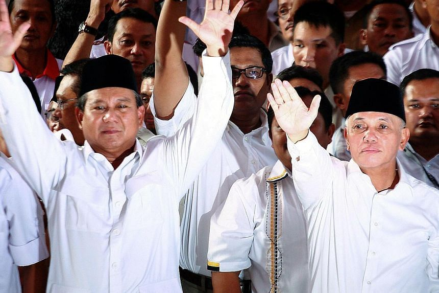 Indonesian presidential candidate Prabowo Subianto (L) and running mate Hatta Rajasa wave to supporters and journalists during a declaration as president and vice president candidates in Jakarta on May 19, 2014. Prabowo Subianto of the Gerindra party