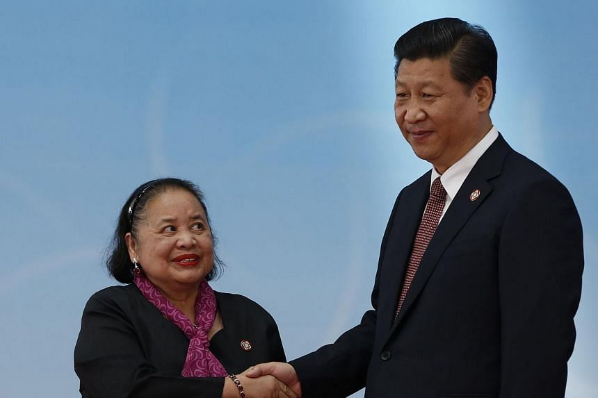 Philippines Ambassador to china Erlinda Basilio (left) and Chinese President Xi Jinping shake hands before the opening ceremony at the Expo Center at a summit in Shanghai on May 21, 2014. Mr Xi issued a veiled warning to the United States on Wednesda