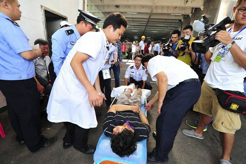 """An injured man (centre) is helped on to a stretcher by medical personnel after leaving the """"Wuzhishan"""" passenger boat that arrived at a port, after picking up Chinese citizens from Vietnam, in Haikou, Hainan province May 20, 2014. -- PHOTO: REUTERS &"""