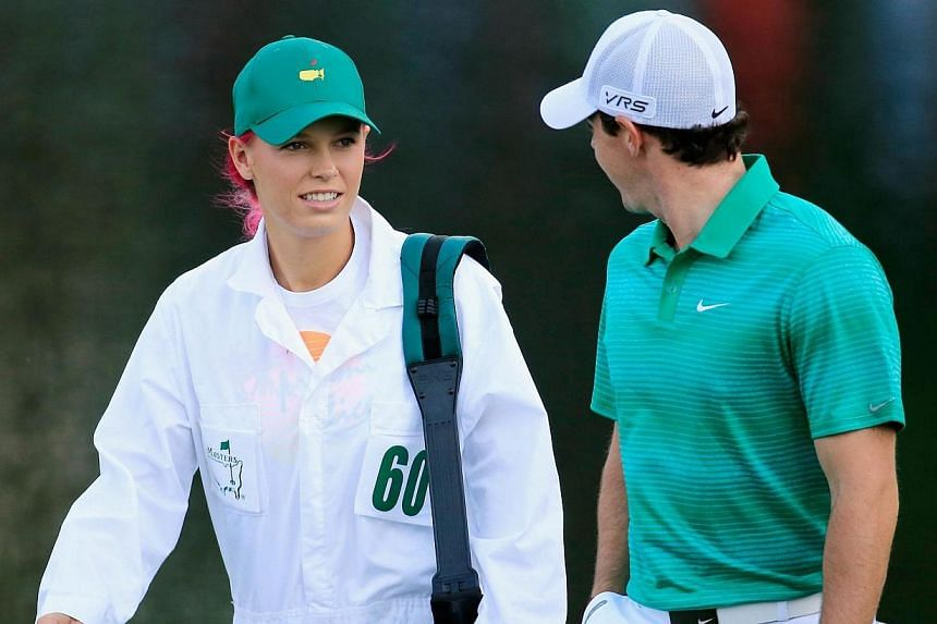Rory McIlroy of Northern Ireland waits with his caddie/girlfriend Caroline Wozniacki during the 2014 Par 3 Contest prior to the start of the 2014 Masters Tournament at Augusta National Golf Club in Augusta, Georgia, on April 9, 2014. World No. 10 gol