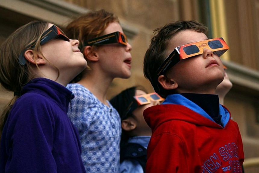 Children wear protective glasses as they try to see a partial solar eclipse from Sydney's Observatory Hill on April 29, 2014.Australian children are among the least active in the world, ranking behind those in Britain and New Zealand, researche