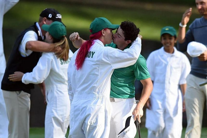 Rory McIlroy kisses his girlfriend, tennis star Caroline Wozniacki, during the Par 3 Contest prior the start of the 78th Masters Golf Tournament at Augusta National Golf Club in Georgia on April 9, 2014. -- PHOTO: AFP