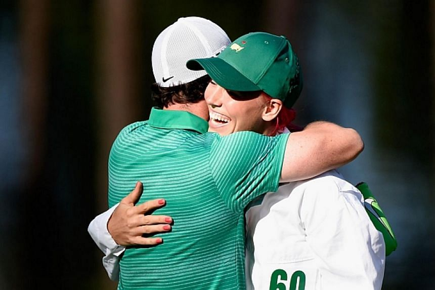 Rory McIlroy hugs his caddie/girlfriend Caroline Wozniacki after she made a birdie putt on the ninth green during the 2014 Par 3 Contest prior to the start of the 2014 Masters Tournament at Augusta National Golf Club in Georgia on April 9, 2014. -- P