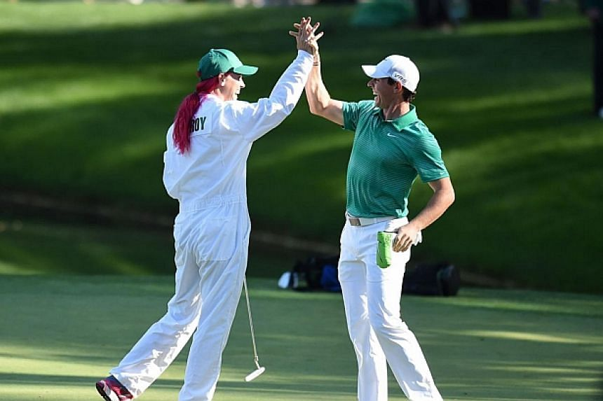 Rory McIlroy celebrates with his girlfriend, tennis star Caroline Wozniacki, on the 9th hole during the Par 3 Contest prior the start of the 78th Masters Golf Tournament at Augusta National Golf Club in Georgia on April 9, 2014. -- PHOTO: AFP