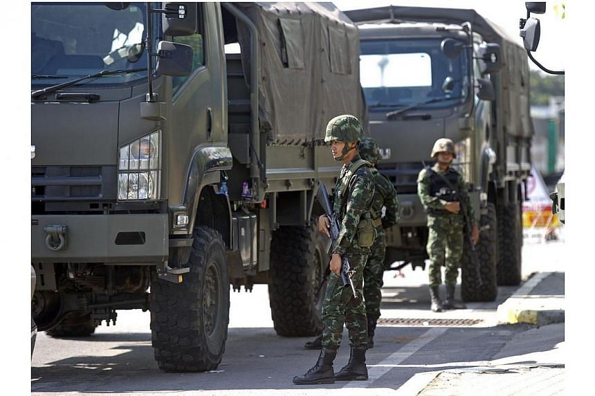 Thai soldiers stand guard near where pro-government are rallying on the outskirts of Bangkok on May 21, 2014.A crisis meeting between leaders of rival Thai political groups aimed at resolving long-running conflict ended inconclusively on Wednes