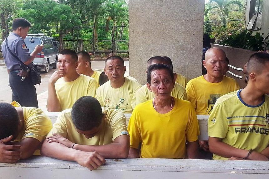 Arrested Chinese fishermen sit with other suspects on charges of illegal fishing while waiting for their arraignment at a court in Puerto Princesa in Palawan island on May 21, 2014.Nine Chinese fishermen arrested by Philippine authorities in di