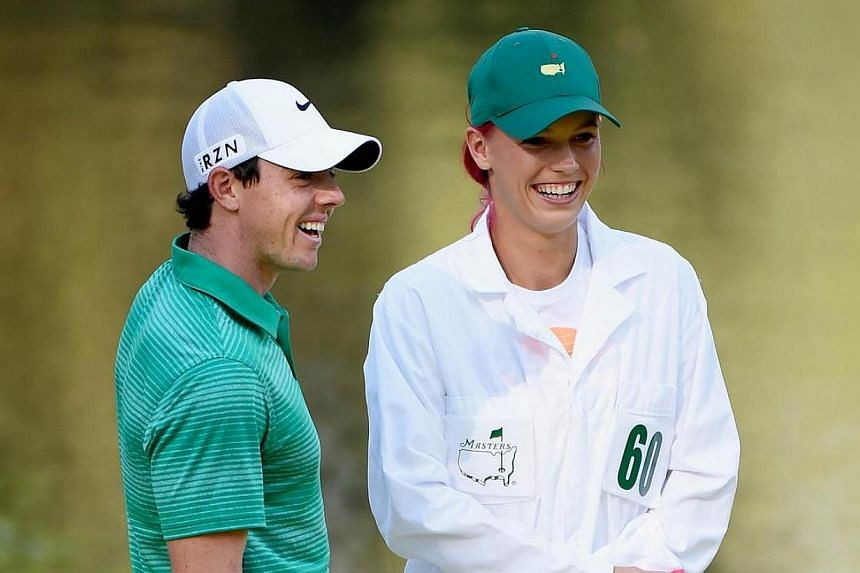 Rory McIlroy of Northern Ireland waits with his caddie/girlfriend Caroline Wozniacki during the 2014 Par 3 Contest prior to the start of the 2014 Masters Tournament at Augusta National Golf Club in Augusta, Georgia, on April 9, 2014. McIlroy called o