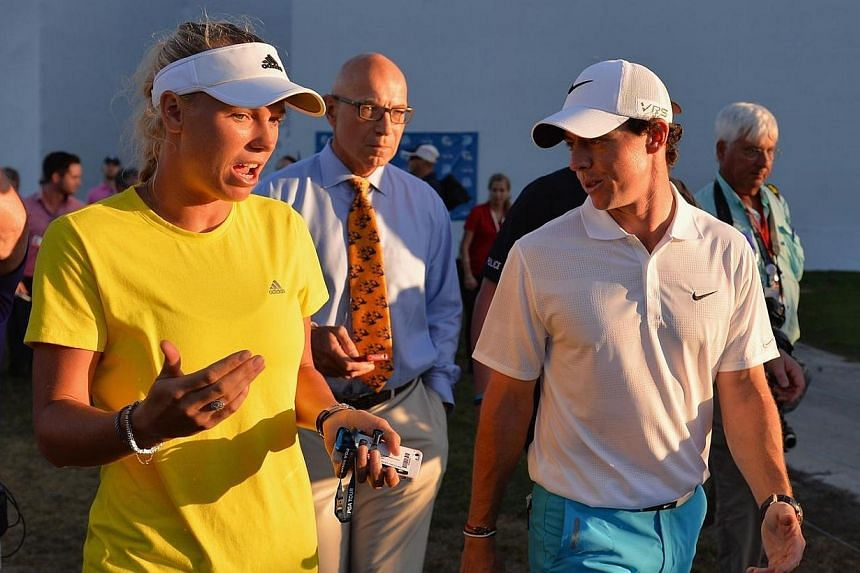 Caroline Wozniacki walks with her fiancee Rory McIlroy following the third round of The Honda Classic at PGA National Resort and Spa in Palm Beach Gardens, Florida, on March 1, 2014. World No. 10 golfer McIlroy called off his engagement to Wozniacki