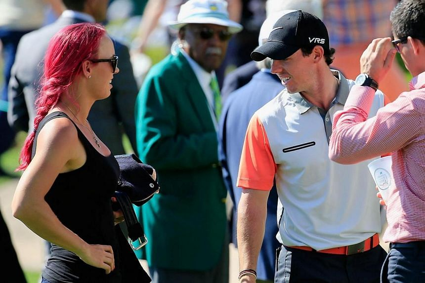Tennis player Caroline Wozniacki chats with her boyfriend Rory McIlroy of Northern Ireland near the clubhouse during the first round of the 2014 Masters Tournament at Augusta National Golf Club in Augusta, Georgia, on April 10, 2014. World No. 10 gol