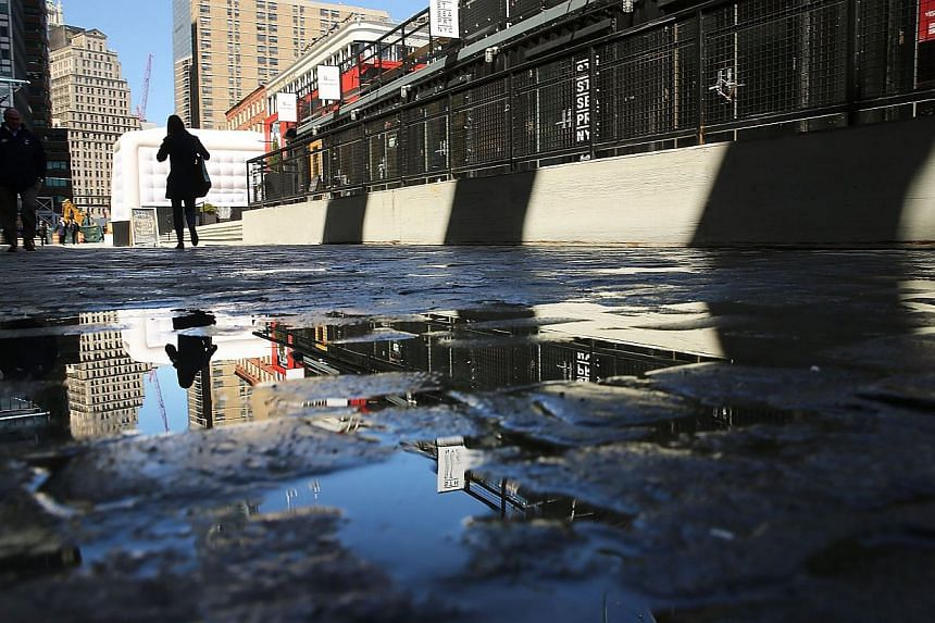 People walk through South Street Seaport, an area of lower Manhattan that was severely flooded during Hurricane Sandy on March 31, 2014 in New York City.Climate change and sea level rise are threatening historic US landmarks, from the Statue of