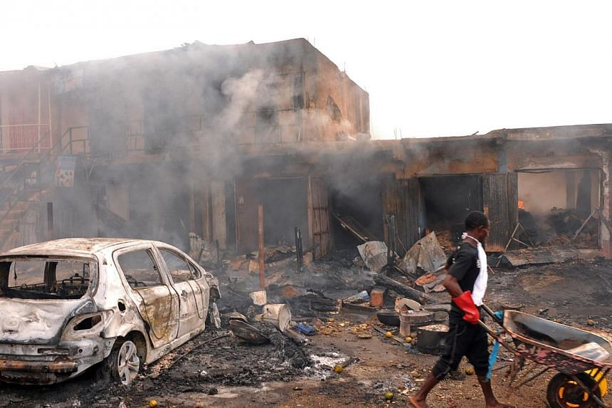 A young boy pushes a wheelbarrow past he wreckage of a burnt vehicle and burning shops following a bomb blast at Terminus market in the central city of Jos on May 20, 2014. -- PHOTO: AFP