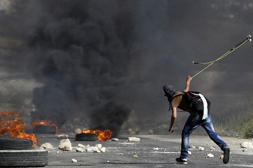 A masked Palestinian demonstrator uses a slingshot during clashes with members of the Israeli security forces outside the Israeli-run Ofer prison in the West Bank village of Betunia, on May 16, 2014, the day after two Palestinian youths were shot dea