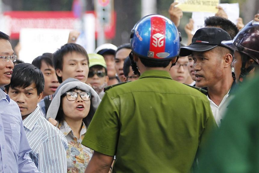 Protesters confronting a policeman as they march during an anti-China protest in Ho Chi Minh City on Sunday. Vietnam flooded major cities with police to avert demonstrations in the wake of deadly rioting in industrial parks that deepened a tense stan