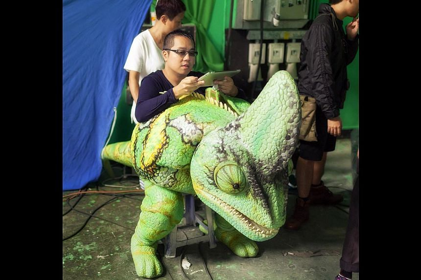 Actress Miriam Yeung (above) rides in a paper car in Aberdeen. Director Pang Ho Cheung (left) in his giant chameleon monster.