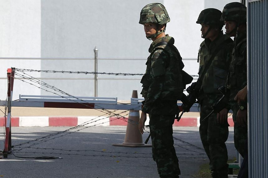 Thai armed soldiers stand guard at the gate of Voice TV satellite tv station office in Bangkok, Thailand, on May 21, 2014. -- PHOTO: EPA