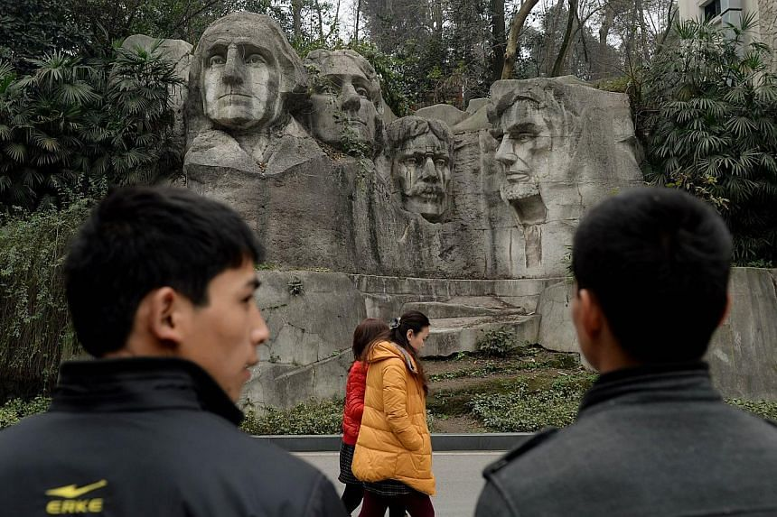 This photo taken on on February 21, 2014 shows people walking past a copy of Mount Rushmore at a park in Chongqing. Already renowned for copying Western goods from trainers to champagne, China is building up its replica reputation with a miniature Mo