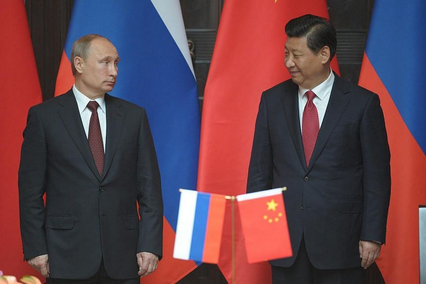 Russian President Vladimir Putin (L) and President Xi Jinping (R) of China attend the ceremony of signing of joint documents after Russian-Chinese talks at the Xijiao state residence in Shanghai, China on 20 May 2014. The two leaders on May 21, 2014&