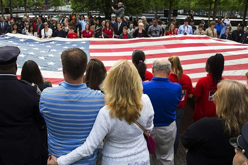 People designated to assist with transferring the National 9/11 Flag, donated by New York Says Thank You Foundation, hold it aloft on the grounds of the 9/11 Memorial Plaza before donating it to the National Sept 11 Memorial Museum in New York on May