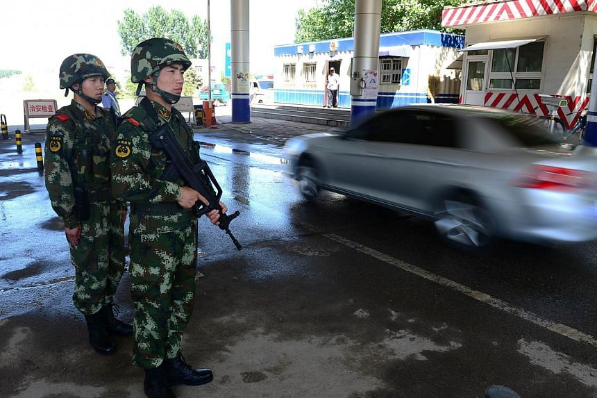 Chinese security personnel guarding a checkpoint along one of the highways leading into Beijing on May 20, 2014. -- PHOTO: AFP