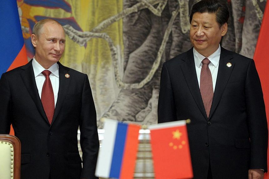 Russian President Vladimir Putin (L) and Chinese President Xi Jinping (R) attend a ceremony of the signing of a China-Russia gas deal in Shanghai, China, on 21 May 2014. -- PHOTO: EPA