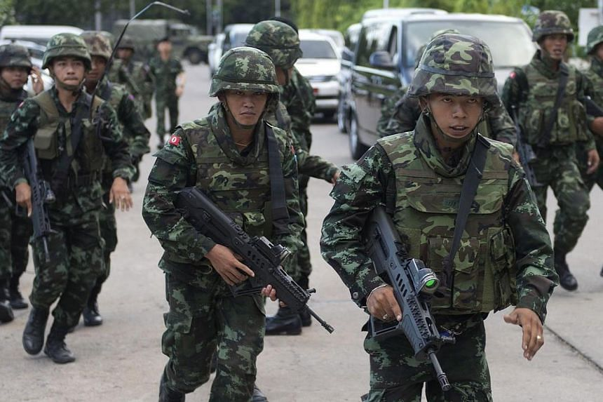 Thai soldiers patrol after army chief General Prayut Chan-O-Cha met with anti-government and pro-government leaders at the Army Club in Bangkok on Thursday, May 22, 2014. Thai soldiers fired into the air to disperse thousands of pro-government,