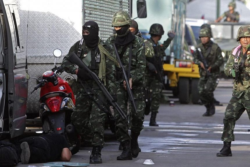 Thai soldiers advance on Red Shirt pro-government supporters rally site on the outskirts of Bangkok, Thailand on May 22, 2014.Singaporehas expressed grave concern over the latest developments in Thailand and urgedall parties involve