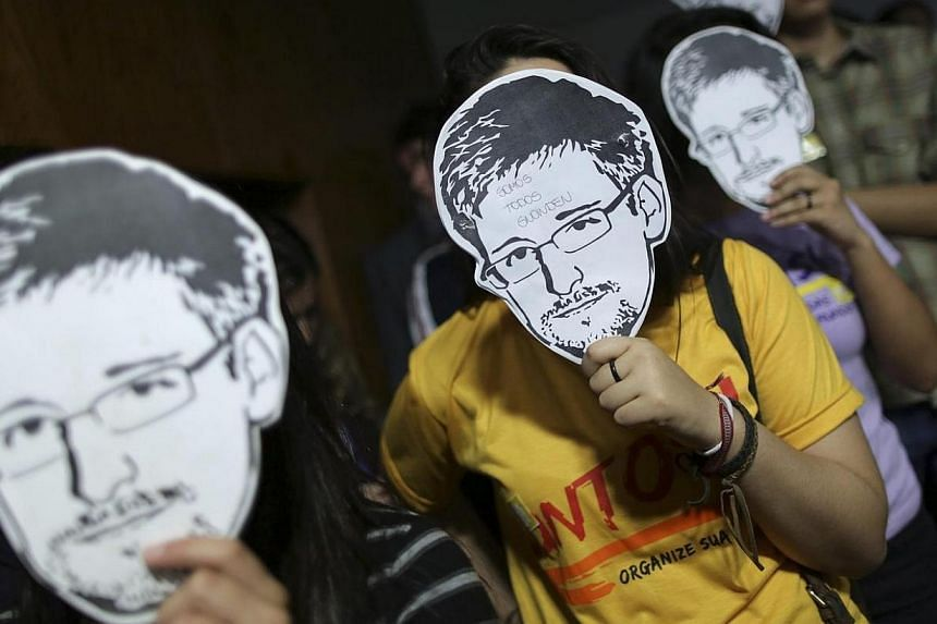 People holds masks with pictures of former NSA contractor Edward Snowden during the testimonial of Glenn Greenwald, the American journalist who first published the documents leaked by Snowden, in Brasilia on August 6, 2013.The House of Represen