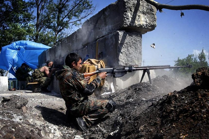 A pro-Russian militant opens fire to test his weapon at a checkpoint outside Slaviansk on May 18, 2014.Separatist rebels on Thursday, May 22, 2014, seized four Ukrainian coal mines in the east of the strife-torn country and demanded that its wo