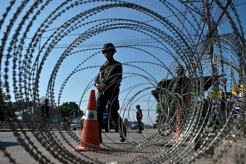 Thai soldiers stand guard at a checkpoint near the pro-government ''Red shirts'' camp site on the outskirts of Bangkok on May 22, 2014. -- PHOTO: AFP
