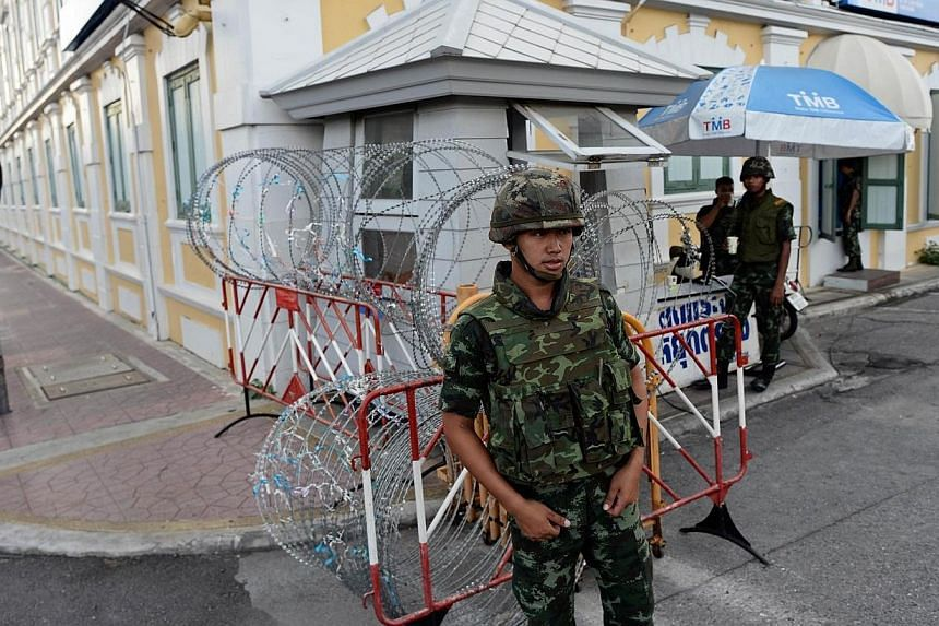 Thai soldiers stand guard at a roadblock outside the Defence Ministry building (background) after Thailand's army chief announced that the armed forces were seizing power, in Bangkok on May 22, 2014. -- PHOTO: AFP