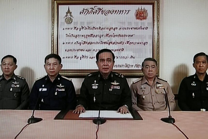 A TV grab shows Army Chief General Prayuth Chan-ocha (centre) speaking next to Navy Chief Adm Narong Pipattanasai (2nd right), Air Chief Marshall Prachin Chantong (2nd left), Thai Police Chief Adul Saengsingkaew (left) and identified high rank milita