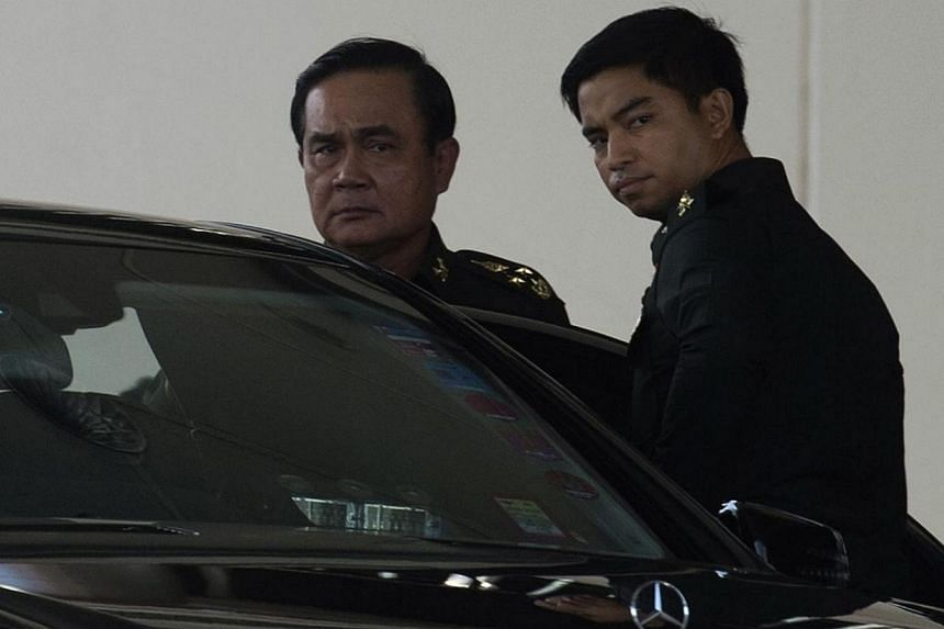 Thailand's army chief Prayut Chan-O-Cha (left) leaves after meeting with anti-government and pro-government leaders at the Army Club in Bangkok on May 22, 2014. -- PHOTO: AFP