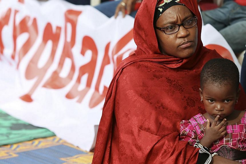 A mother and her daughter join protesters in a sit-in protest demanding the release of abducted secondary school girls in the remote village of Chibok, opposite Maitama park, in Abuja on May 10, 2014. The United States deployed 80 military personnel