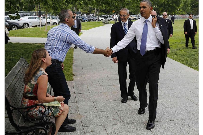 US President Barack Obama shakes hands with Israeli tourists while walking on the Ellipse with White House counselor John Podesta near the White House in Washington on May 21, 2014. -- PHOTO: REUTERS