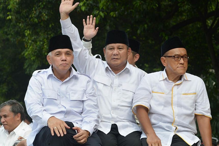Indonesian presidential candidate Prabowo Subianto (centre) waving to supporters. He is flanked by his running mate Hatta Rajasa (left) and Golkar chairman Aburizal Bakrie. The presidential race is a head-to-head contest between two new political pla