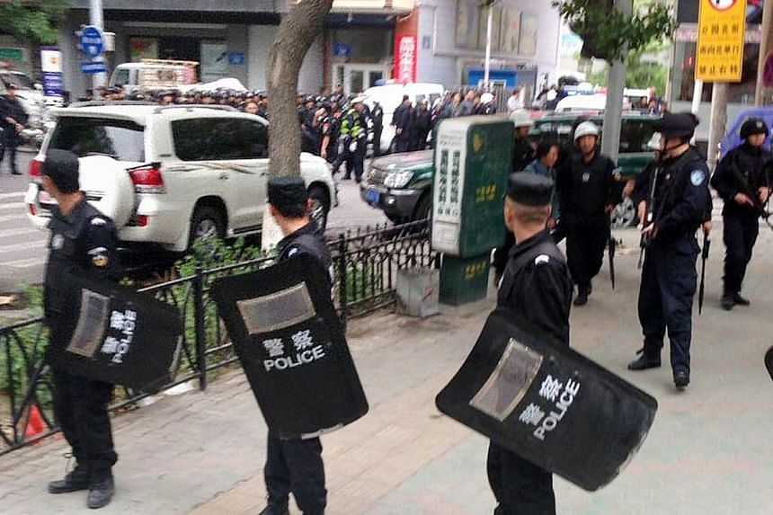 Riot policemen look behind them toward the site of an explosion, which has been cordoned off, as they stand guard in downtown Urumqi, Xinjiang Uighur Autonomous Region, May 22, 2014 in this photo distributed by China's official Xinhua News Agency. --