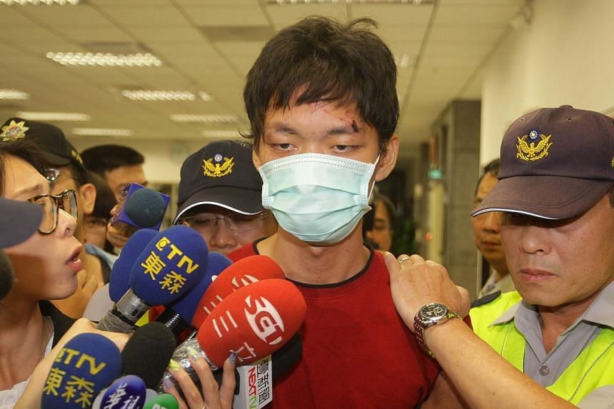 The alleged attacker Cheng Chieh (centre) is transferred by policemen at a local police station in New Taipei City on May 22, 2014. -- PHOTO: AFP