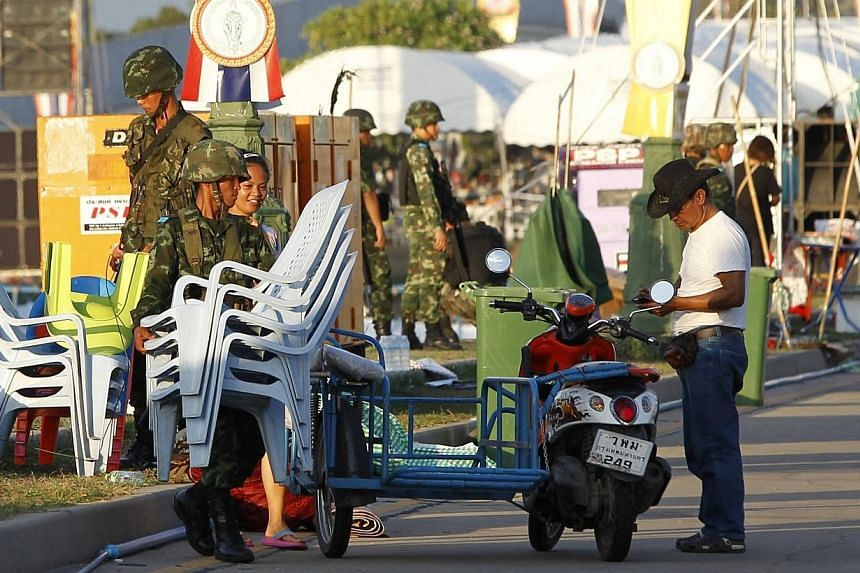 """A Thai soldier carries chairs past a member of the pro-government """"red shirt"""" group at an encampment in Nakhon Pathom province on the outskirts of Bangkok on Thursday, May 22, 2014. -- PHOTO: REUTERS"""