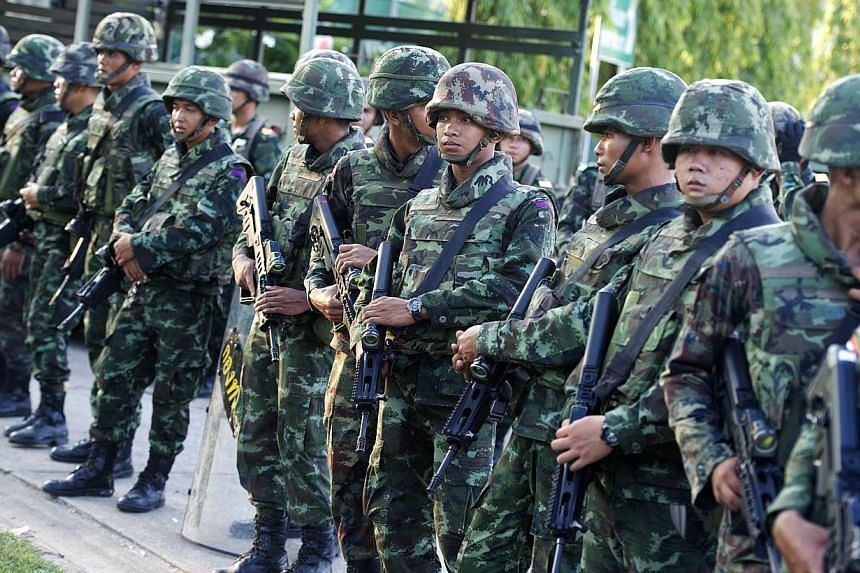 Thai soldiers stand guard after army chief General Prayut Chan-O-Cha met with anti-government and pro-government leaders at the Army Club in Bangkok on Thursday, May 22, 2014. -- PHOTO: AFP