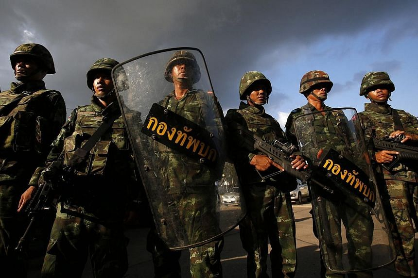 Thai soldiers stand guard during a coup at the Army Club where Thailand's army chief held a meeting with all rival factions in central Bangkok on Thursday, May 22, 2014. Thailand's military on Thursday declared a night-time curfew across the troubled