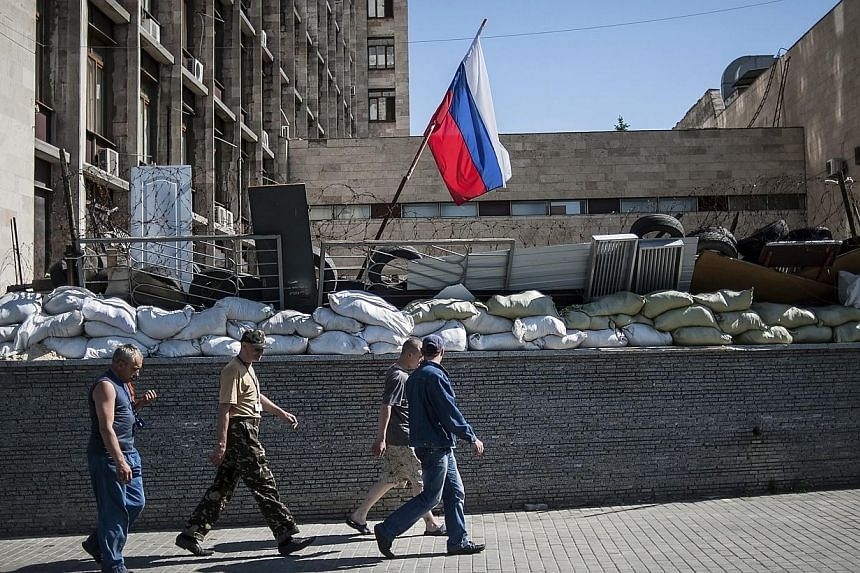 People pass under a Russian flag in front of the occupied administration building in Donetsk, Ukraine on May 21, 2014. -- PHOTO: EPA