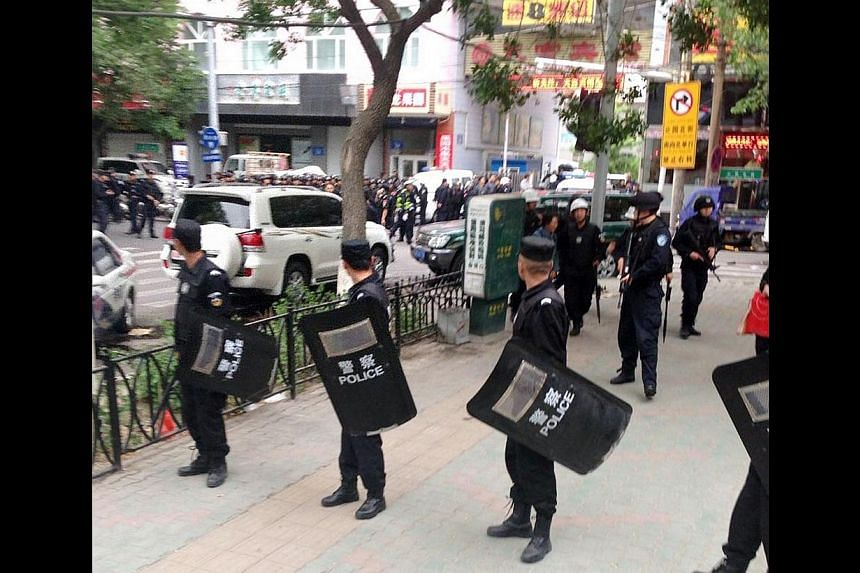 Riot policemen look behind them toward the site of an explosion, which has been cordoned off, as they stand guard in downtown Urumqi, Xinjiang Uighur Autonomous Region on May 22, 2014, in this photo distributed by China's official Xinhua News Agency.