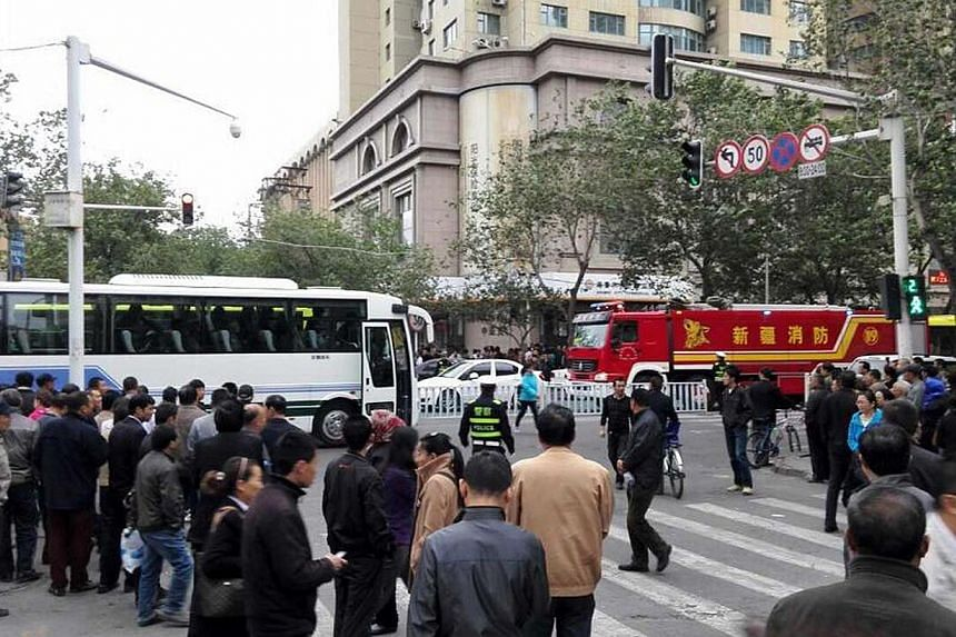Residents gather to watch as police seal off the site where attackers ploughed two vehicles into a market and threw explosives, killing at least 31 people, in Urumqi in northwest China's Xinjiang region on May 22, 2014. -- PHOTO: AFP