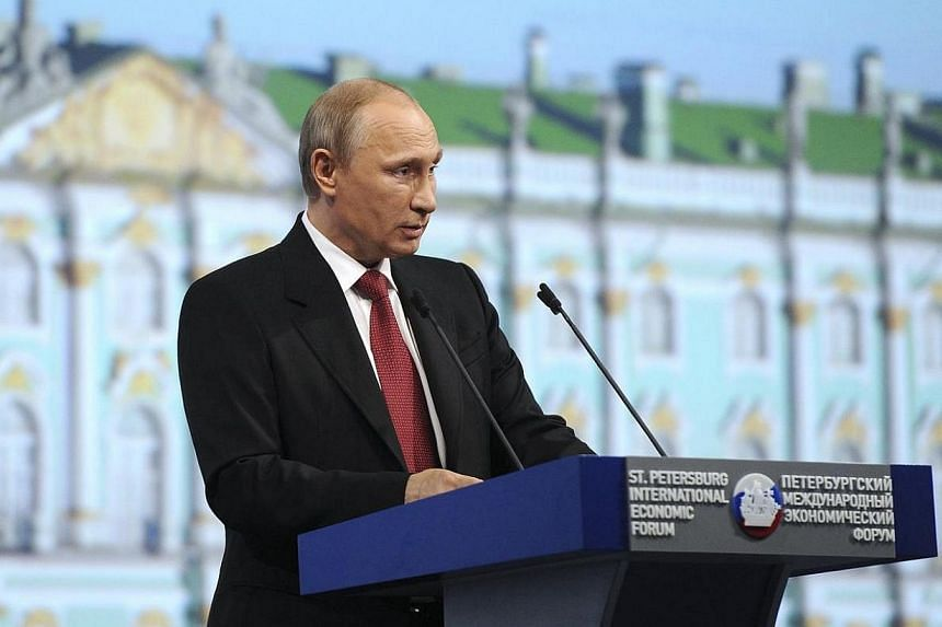 Russia's President Vladimir Putin speaks during a session of the St Petersburg International Economic Forum 2014 in St Petersburg on May 23, 2014. Mr Putin said on Friday, May 23, 2014, he was upbeat on the prospects for resolving the crisis in