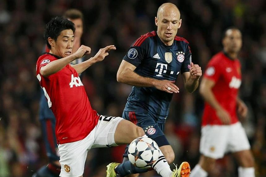 Manchester United's Shinji Kagawa (left) fights for the ball with Bayern Munich's Arjen Robben during a Champions League match at Old Trafford on April 1, 2014.Kagawa says he will not use the World Cup to impress United's new manager Louis van